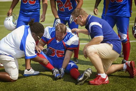 football player injured on field with athletic trainer